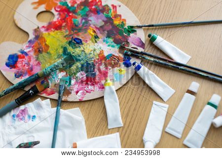 fine art, creativity and artistic tools concept - close up of palette, brushes and paint tubes on table