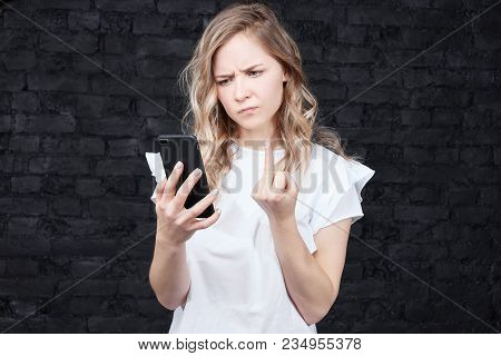 Blonde Woman With Long Hair, Angry Expression, Shows Middle Finger To Boyfriend Who Is Calling On Ph