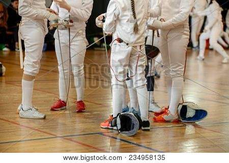Girls, Participants In Fencing Competitions On Swords Stand In The Center Of Fencing Hall Waiting Fo