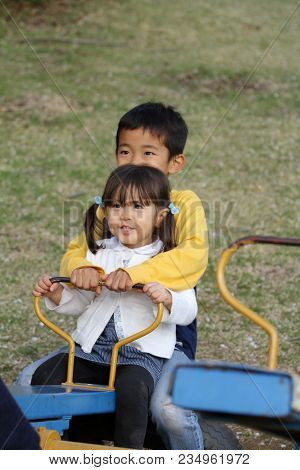 Japanese Brother And Sister On The Seesaw (8 Years Old Boy And 3 Years Old Girl)