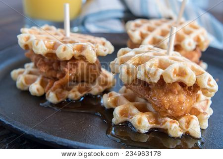 Three Chicken And Waffle Sliders With Syrup On Cast Iron Skillet