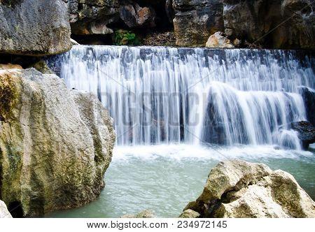 Aquatic Waterfall In The Rock Cliffs River