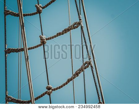Old Fashioned Mast Rigging, Many Brown Ropes On Clear Blue Sky Background.