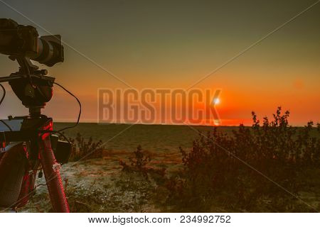 Professional Camera On Tripod Taking Picture Film Video Of Sunrise Over Sea Surface, Greece