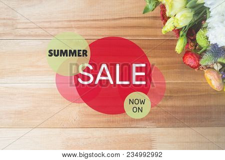Red and green circular sale graphic on table with flowers