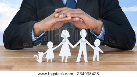 Cut outs of family under protective hands
