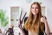 Young woman with hair straightener at home poster