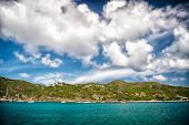 Holiday destination while travelling and wanderlust. Mountain shore in blue sea on cloudy sky in gustavia, st.barts. Summer vacation on tropical island. Wild nature and environment, ecology. poster
