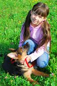 Smiling girl kneeling in grass with a young German Shepherd beside her. poster