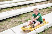 Cute smiling young boy riding downhill on an alpine coaster ride outdoors on a summers day. Happy and having fun on a thrilling theme park ride poster