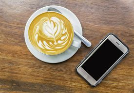 Cup Of Latte Art Coffee With Smart Phone.