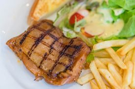Medium Rare Grilled Beef Steak On On Wooden Black Background With French Fries And Ketchup,