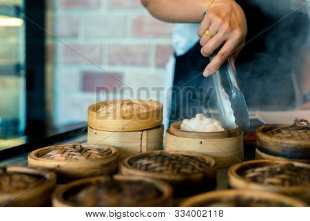 Dim Sum In Bamboo Steamer Chinese Cuisine. Close Up Woman Female Hands Holding Tongs Choosing Meal D
