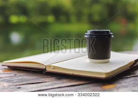 Little Cup Of Coffee On The Book Near The River.