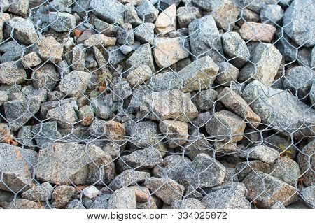 Gabion Wall Closeup. Textured Background. Gabion Is Stones In Wire Mesh Used For Erosion Control.