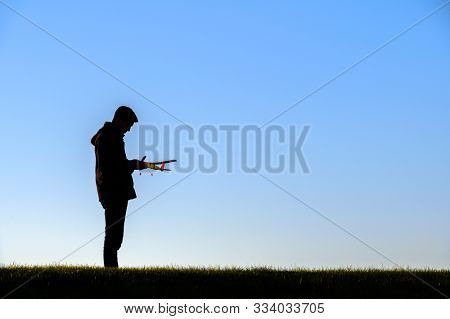 Young man holding a model airplane against a beautiful sunsel