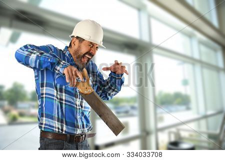 Construction worker getting hurt with saw at work inside a building