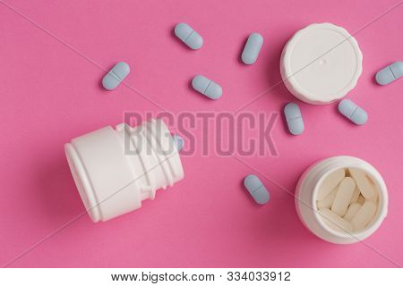 White Pill Bottles On A Pink Background And Scattered White And Blue Tablets
