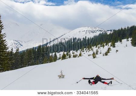 Ukraine, Hoverla - April 22, 2017. High In The Mountains, A Man Lies On His Back In The Snow With Hi