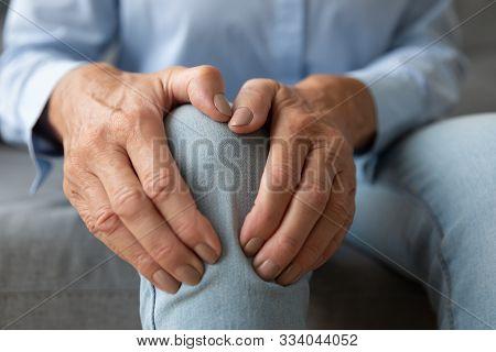 Old Woman Touching Knee Feeling Pain Suffering From Osteoarthritis, Closeup