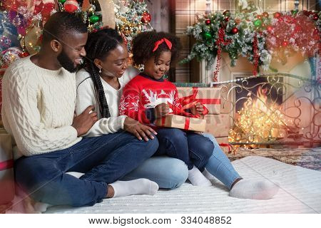 Family Christmas Concept. Cute Little Black Girl Opening Gift Box On Christmas Eve While Sitting On