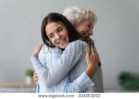 Happy Young Granddaughter Embracing Hugging Old Retired Grandmother Cuddling