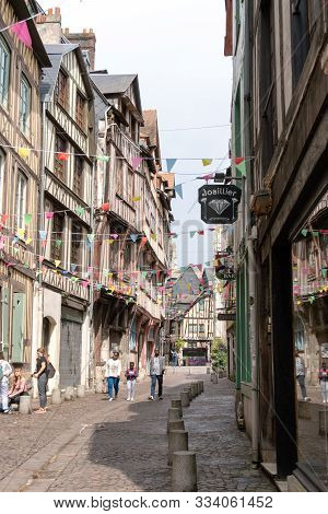 Tourists Visit The Historic Old City Center Of Rouen In Normandy With Hits Famous Half-timbered Hous