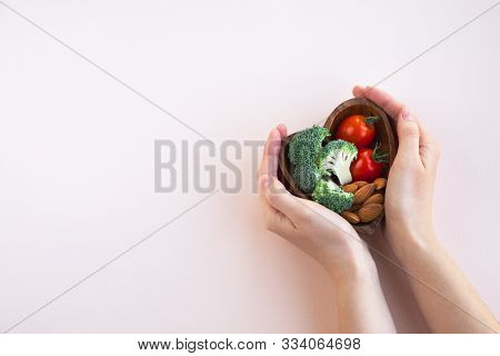 Healthy Food For Heart On Light Background. A Plate With Vegetables And Nuts In A Woman`s Hands. Die