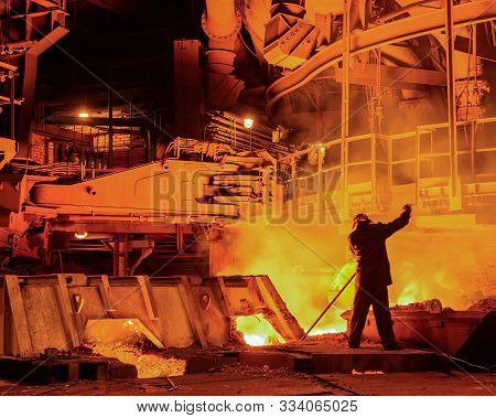 For The Blast Furnace With Liquid Steel Inside, Heavy Industry Concept. Machinery And Workers At The