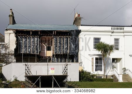 Storm Damaged House With A Collapsed Front Showing The Rooms Inside, Swansea, Wales, Uk, November 20