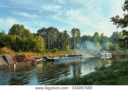 A Tug Hauling Two Cargo Barges On The Warta River In Poland