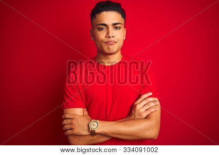 Young brazilian man wearing t-shirt standing over isolated red background skeptic and nervous, disapproving expression on face with crossed arms. Negative person.