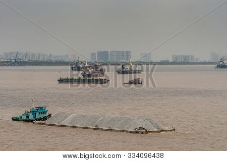 Long Tau River, Vietnam - March 12, 2019: Small Blue Boat Pushes Long Barge Filled With Gray Stones