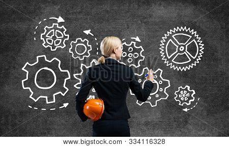 Businesswoman Draws Cogwheel Mechanism On Chalkboard. Woman In Business Suit With Safety Helmet. Mec