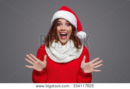 Excited Eccentric Female In Red Santa Hat And Colorful Knitwear Screaming With Open Palms Looking At