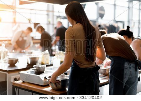 Culinary Class. Back View Of The Process Of Cooking. Different Unrecognizable People In Gray Apronst
