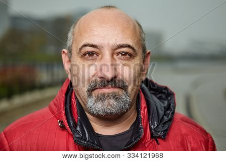 Close Up Portrait Of A Bald Man With A Gray Beard Outdoors In Cloudy Weather. Mature Adult Male In A