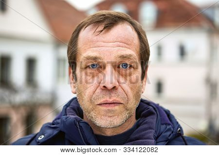 A Serious Face Of A Caucasian Middle-aged Man, Over 50, Close-up, He Is An Emigrant, Unemployed, Or