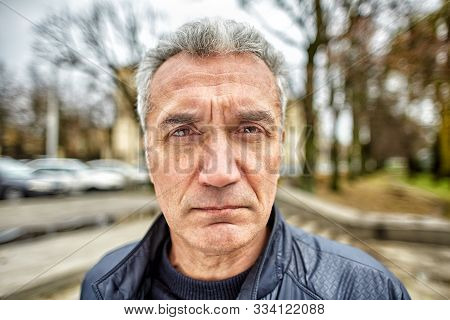 A Gray-haired Man With A Short Haircut Over 50 Years Old, Carefully Looks In Front Of Him Outdoors,