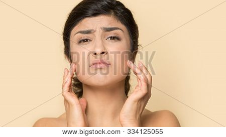 Head Shot Unhappy Indian Female Touching Skin, Worried About Blemishes