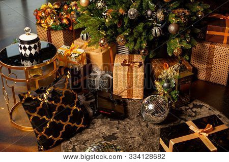 Close-up Of A Christmas Tree Decorated With Gold Balls. Under The Christmas Tree A Large Number Of C