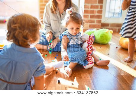 Beautiful teacher and group of toddlers playing around lots of toys at kindergarten