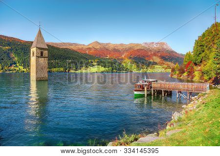 Fantastic Autumn Lake Landscape With A Ship Near The Pier And  Submerged Bell Tower In Lake Resia. L