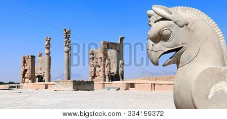 Stone sculpture of griffin and Gate of All Nations (Xerxes gate) in the ancient city of Persepolis, Iran. UNESCO World heritage site. On blue sky background