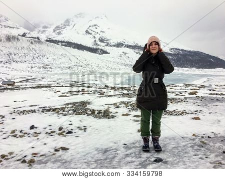 A Young Female Hiker Posing In Front Of The Athabasca Glacier Along The Columbia Icefield Parkway In