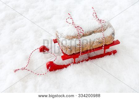 Dresdner Stollen, A German Christstollen, On Red Wooden Sledge In Snow With Copy Space. High Angle V