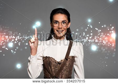 Excited Attractive Steampunk Woman Showing Idea Sign Isolated On Grey With Glowing Illustration