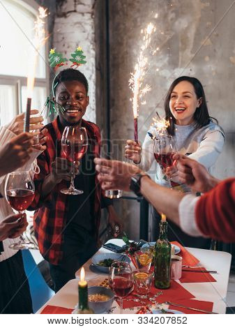 Group Of Friends Toasting Drinks At A Party. People Having Wine Indoors On A Winter Holidays