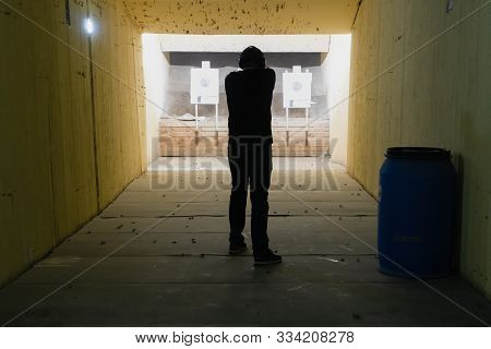Man In Shooting Range In Shooting Action With Glock 19, View From Behind O Holding A Pistol Taking A