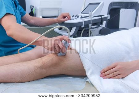 Doctor Makes Ultrasound Of Knee Joint To Man Using Ultrasound Scanner In Clinic, Closeup Leg View. H